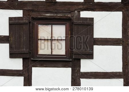 Detail Of White Half-timbered Cottage Window With Shutters.
