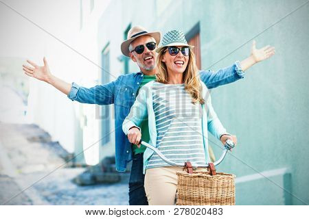 Mature couple enjoying while riding bicycle by building