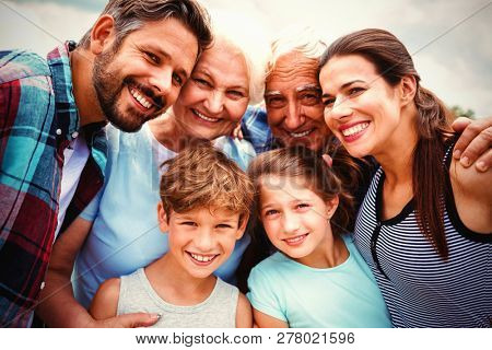 Portrait of happy multi generation family standing against sky