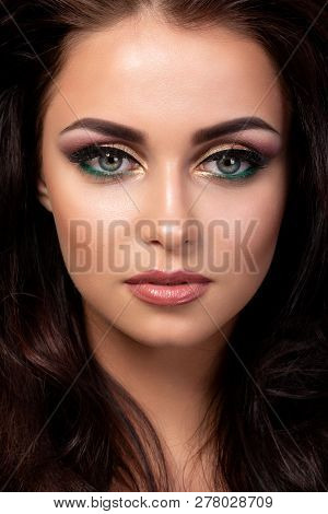 Portrait Of Young Beautiful Woman With Evening Make Up Posing Over Black Background. Red And Gold Mu