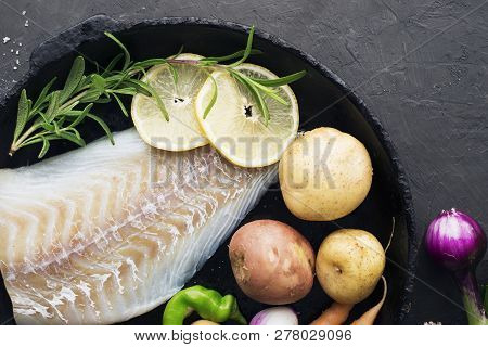 Cod. Fresh Sea White Raw Fish Before Cooking In A With Fresh Vegetables: Sweet Onions, And Lemons. T