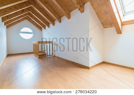 empty spacious and bright attic in a refurbished apartment with wooden parquet floor and white walls and wooden gable roof poster