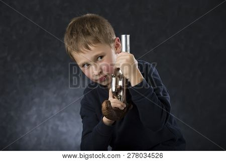 Boy With A Gun. The Child Plays With The Weapon. Six Seven Year Old Toddler With Retro Boob