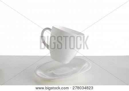 White Cup With Saucer In A Jump On A White Background. Jumping Cup. Flying Dishes On A White Backgro