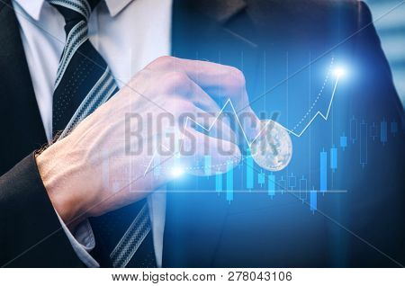Close Up Hand Of Investor Business Man Pick Bitcoin From Suit Pocket With Graphic Candle Stick Graph