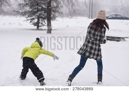 Mom and son playing snowball fight and smiling in winter.  Happy family (mother and son) having fun on snow poster