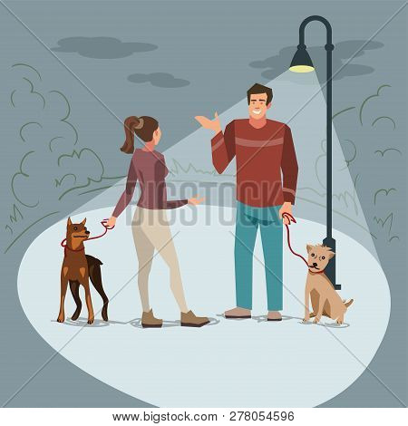 Young People (man And Woman) Walk In The Park With Their Dogs In The Evening When Lighted Lanterns.