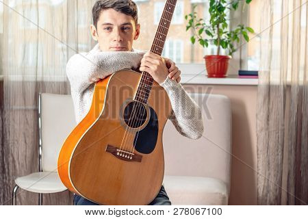 Young Attractive Male Musician Sitting On A Chair Holding An Acoustic Guitar. Concept Of Music As A