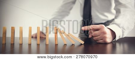 Chain Reaction In Business Concept, Businessman Just Starting Dominoes Toppling