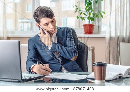 Businessman Sitting At The Table Signing Documents In The Office. Concept Of Transactions And Work W