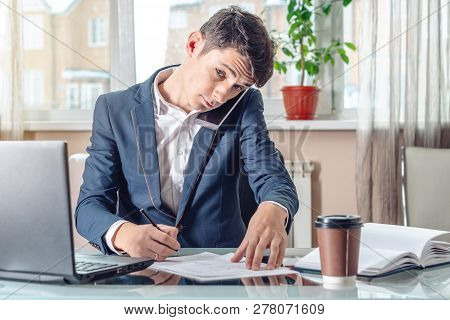 Businessman Sitting At The Table Signing Documents In The Office. Concept Of Transactions With Secur