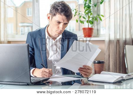 Businessman Sitting At The Table Signing Documents In The Office. Registration And Transactions With