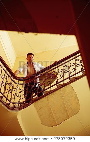 Man Stand High On Staircase. Businessman Climb Stairs. Sexy Macho In Open Shirt With Bare Torso On S