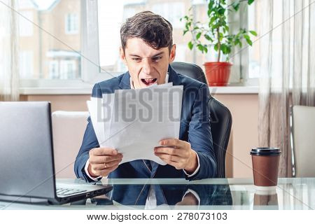 Male Businessman Sitting At A Work Place Examing Documents. Concept Of The Office Working With Docum