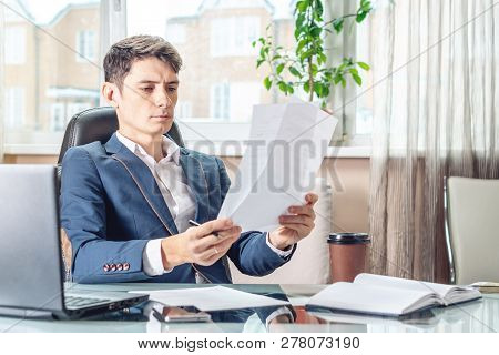 Male Manager Sitting At A Work Place Examing Documents. Concept Of The Office Working With Documents