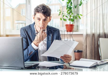 Male Lawyer Sitting At A Work Place Examing Documents. Concept Of The Office Working With Documents