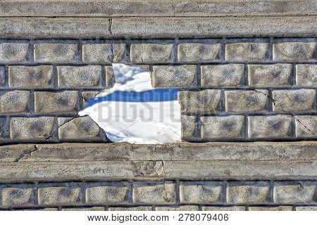 A Big Hole With Cracks On A Gray Concrete Wall Of A Fence