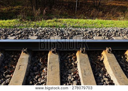 Part Of The Railroad With An Iron Rail And Concrete Sleepers In Small Gray Rubble And Green Grass On