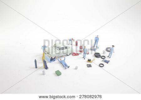 A Mini People Worker Repairing Wheel Of Car