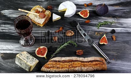 Red And White Wine Plus Different Kinds Of Cheeses Cheeseboard On Rustic Wooden Table. French Food T