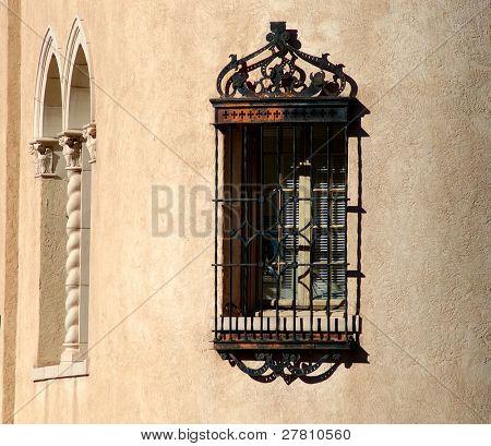 Ornate iron grated window in adobe wall