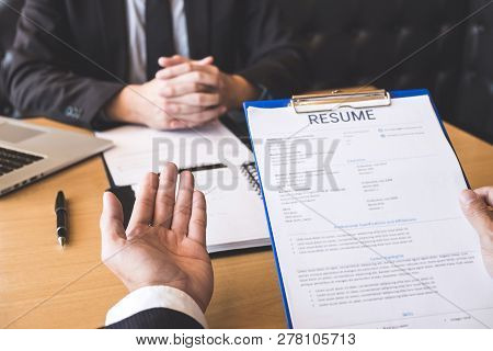 Employer Or Recruiter Holding Reading A Resume During About His Profile Of Candidate, Employer In Su