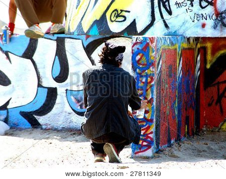 Young man painting graffiti on n ever changing public tag wall. It is painted new daily