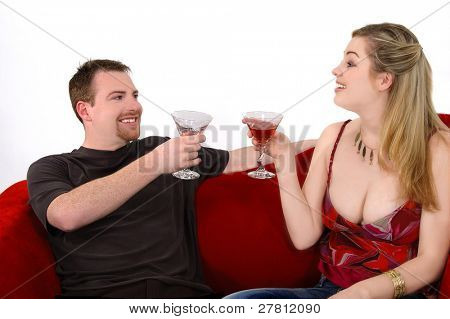 Young urban couple raise a toast on a velvet couch at a casual martini party