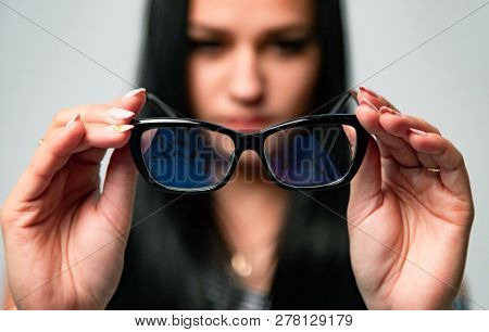 Portrait Of Woman On Blurred Background Holding Focused Protective Optical Eyeglasses Isolated In St