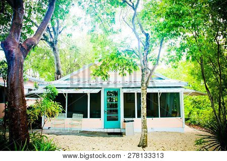 Tropical Bungalow Surrounded By Tropical Trees And Painted With Pastel Colors. The Small House Is Pa