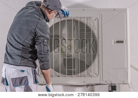 Modern Heat Pump Repair By Caucasian Technician In His 30s. House Heating Technologies.