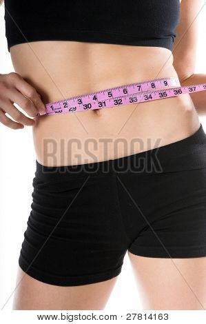 A woman in workout clothing measuring her waistline with a cloth tape measure