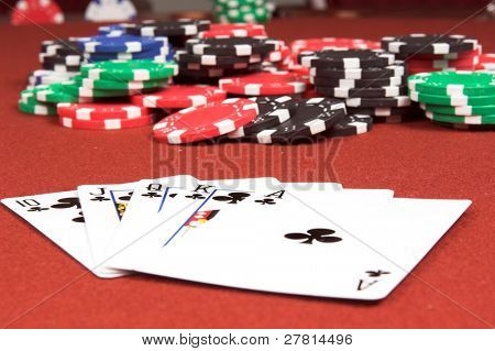 One of the highest hands in poker a Clubs Royal Flush on a red felt gaming table with a poker jackpot in the background