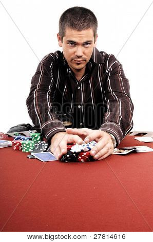 A man playing Texas Holdum Poker collects his winnings Card backs are a digitally created design