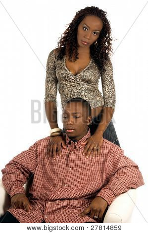 Sexy African American woman in a casual denim skirt and snake skin print top standing by a man sitting in a white chair