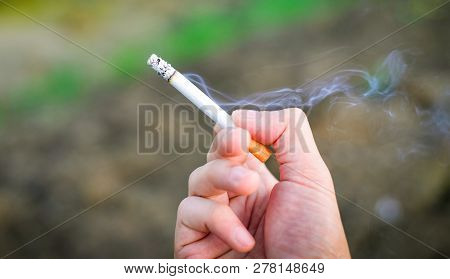 Cigarette In Hand / Cigarette Smoke Burning On Hand Man Smoking On Outdoors Background