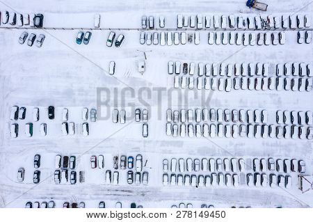 Winter Parking Lot With Cars And Vacant Parking Places. Aerial View