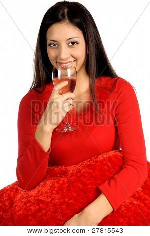 Beautiful latina woman in a red  with a big Valentine's Day   red heart shape pillow and a glass of wine