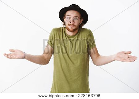 Have No Idea What Talking About. Confused Unsure Handsome Young Bearded Male In Hat And Glasses Smir
