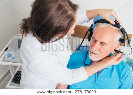 Senior Man Having Hearing Exam At Audiologists Office