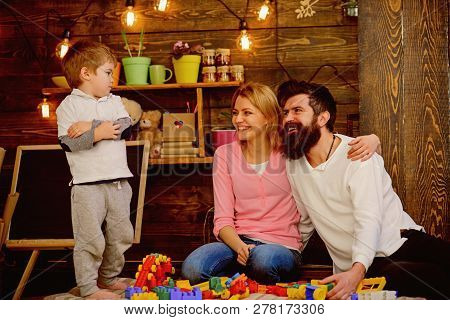 Play Concept. Little Child With Mother And Father Play With Toy Bricks. Creative Family Play. The Be