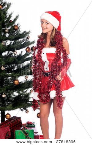 Sexy Ms. Santa Claus by the Christmas tree draped in a tinsel garland