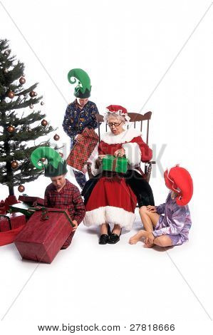 A group of children gathered around the Christmas Tree with their gifts and Mrs. Santa Claus sitting in her rocking chair.