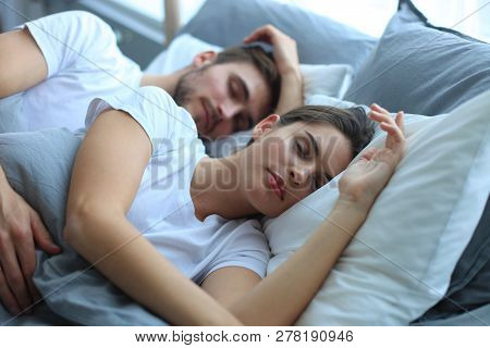 Happy Couple Sleeping In A Comfortable Bed At Home.