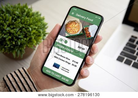 Female Hand Holding Touch Phone With App Delivery Food On The Screen Above The Table In The Office