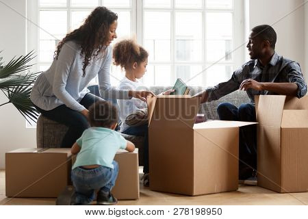 African American Kids Helping Parents Unpacking Boxes In Living