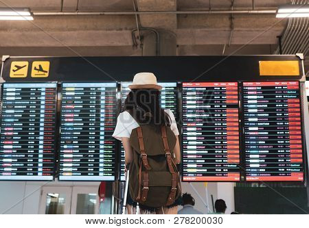 Asian Woman Traveler Looking Information Board With Carrying, Suitcase Luggage And Passenger For Tou