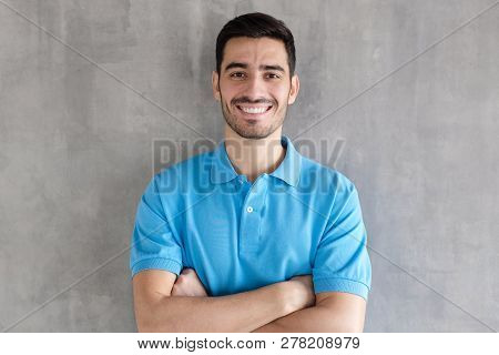 Smiling Handsome Man In Blue Polo Shirt Standing With Crossed Arms, Standing Against Gray Textured W
