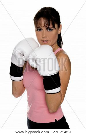 Healthy young woman in white boxing glove takes her fighting stance during a boxing workout.
