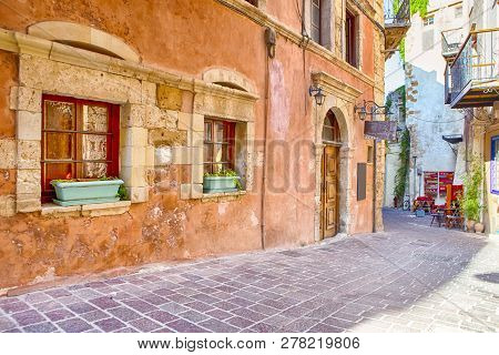 Tranquil And Empty Street Of Chania At Summer Time With Colorful Shutters At Windows And Flowers In